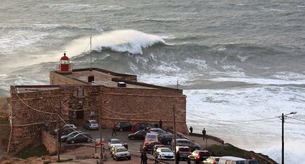 Big wave in Nazare and the lighthouse