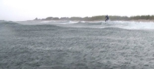 surfer riding a wave in the rain
