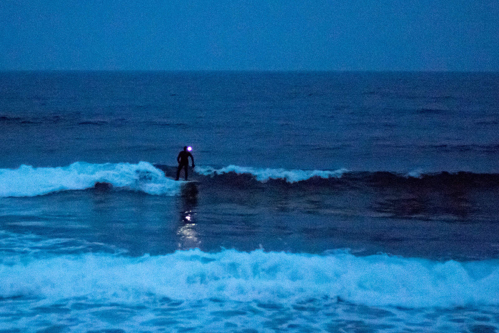 Night surfing with a headlamp. Photo: Miha Godec